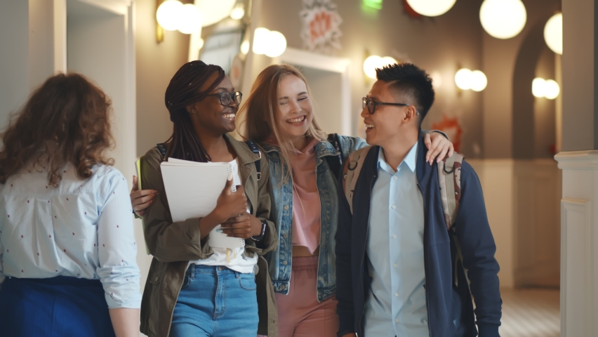 Positive diverse group of young and stylish students going home after lecture on long corridor. Happy multiethnic students hugging walking in hallway of university building Royalty-Free Stock Footage #1062412597