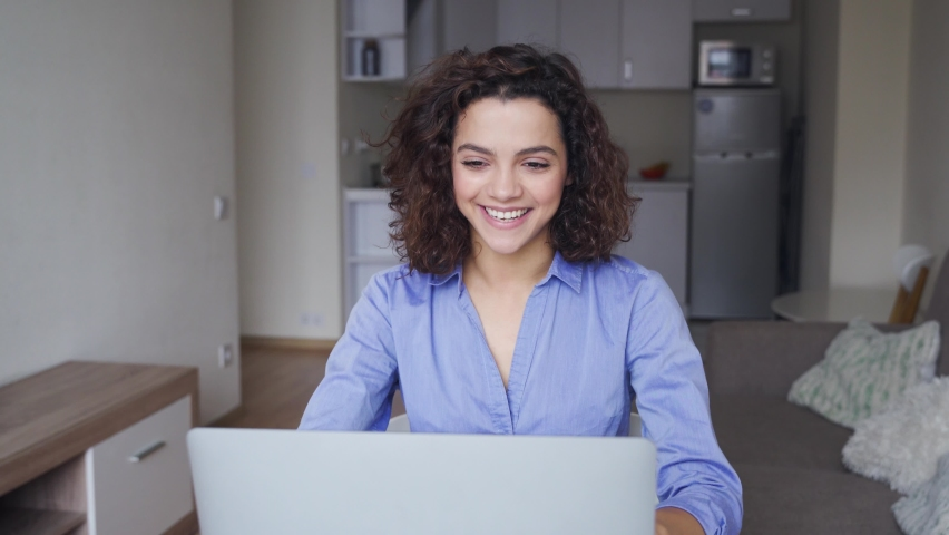 Happy latin gen z young woman, female student with curly hair talking with friends using laptop computer, making video call conference in virtual webcam, online dating, chat sitting at table at home. Royalty-Free Stock Footage #1062413926