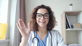 Attractive young female doctor wear eyeglasses make online video call consult patient on laptop. Medical assistant therapist videoconferencing. Web camera view. Telemedicine pandemic concept.
