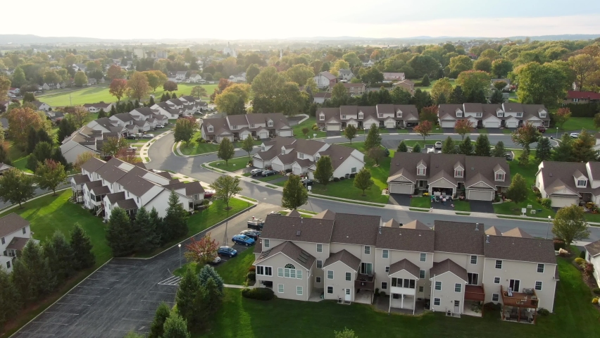 Townhouse condo apartment buildings during magic hour. Aerial drone shot above uniform tan brown houses in neighborhood community in USA. Royalty-Free Stock Footage #1062415273