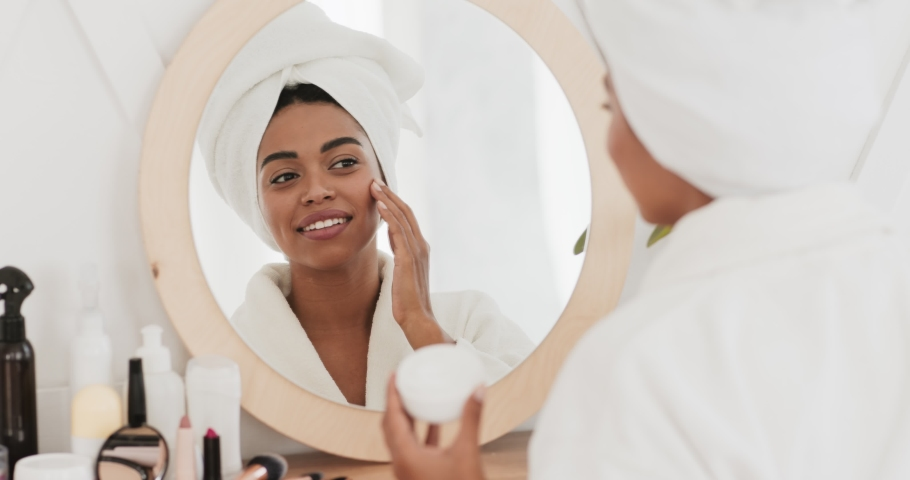 Feminine daily procedures. Young african american lady in bathrobe applying cream on face, moisturizing skin after morning shower, slow motion Royalty-Free Stock Footage #1062422659