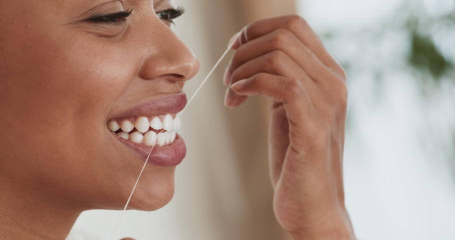 Intensive tooth care. Young black woman flossing her teeth with tooth floss at home, close up portrait Royalty-Free Stock Footage #1062422662