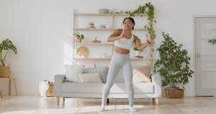Training muscles priests and legs in dance. Energetic african american lady dancing after fitness workout at home, enjoying her lifestyle, slow motion