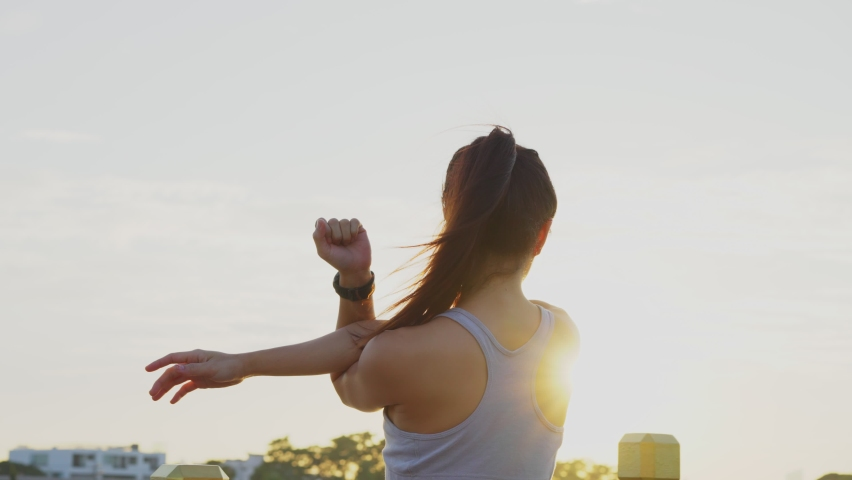 New normal sport outdoor, young Asian fit sport woman stretching her body warm up before workout outdoor. The girl in sportswear exercises outside in the evening sunset for health and wellbeing. | Shutterstock HD Video #1062424663