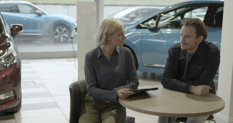 Saleswoman advising male on car purchase in vehicle dealership showroom using digital tablet