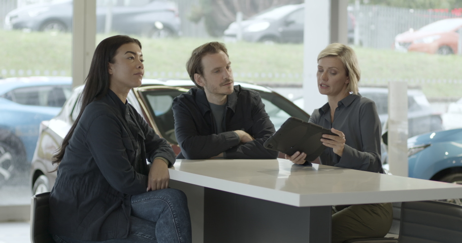 Saleswoman advising couple on car purchase in vehicle dealership showroom using digital tablet