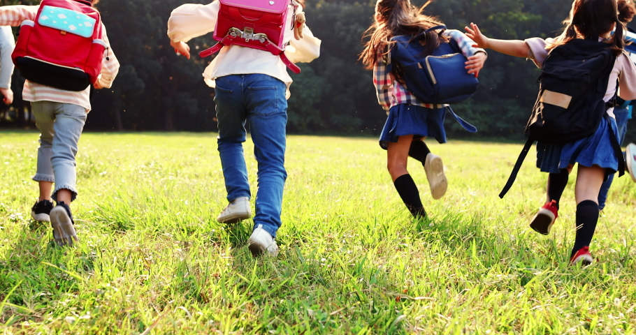 rear view of elementary school kids running on the grass Royalty-Free Stock Footage #1062426421
