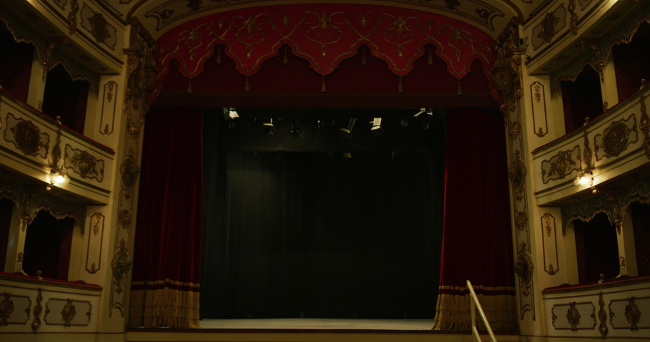 Cinematic shot of empty classic theatre with red velvet curtains opening stage with dramatic lighting before start of show. Royalty-Free Stock Footage #1062430972