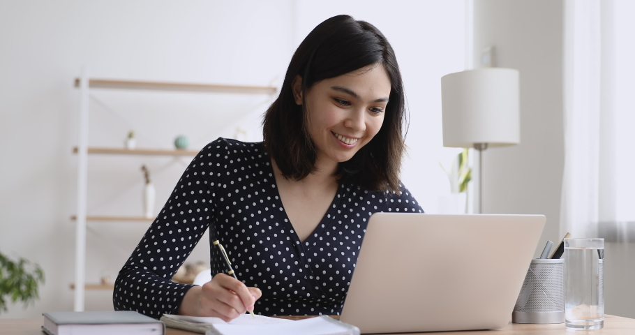 Happy millennial asian korean female student studying distantly using computer application, listening educational lecture, attending online class, checking homework, preparing for exams, writing notes Royalty-Free Stock Footage #1062431269