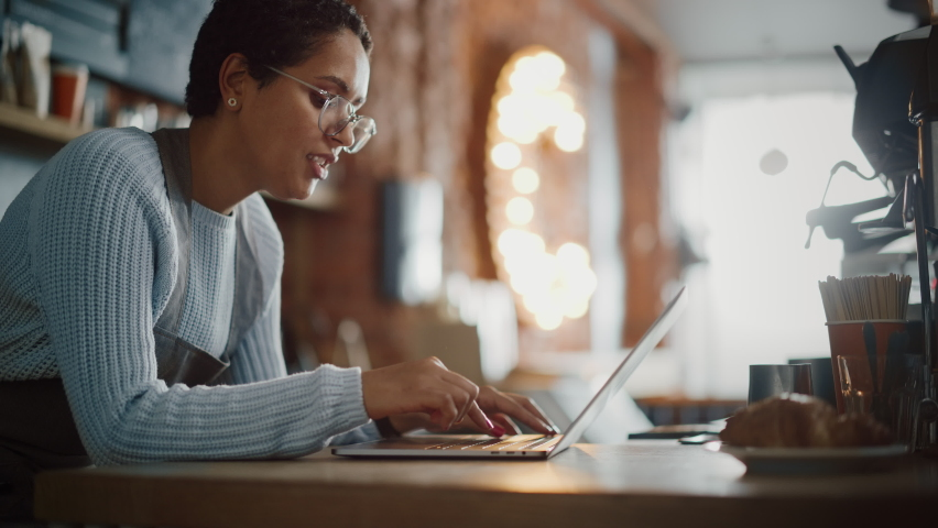 Young and Beautiful Latina Coffee Shop Owner is Working on Laptop Computer and Checking Inventory in a Cozy Cafe. Successful Small Business Owner Browsing Internet and Accepting Take Away Orders. Royalty-Free Stock Footage #1062437044