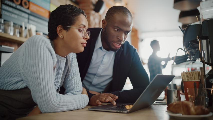 Two Diverse Entrepreneurs Have a Team Meeting in Their Stylish Coffee Shop. Barista and Cafe Owner Discuss Work Schedule and Menu on Laptop Computer. Multiethnic Female and Male Restaurant Employees. | Shutterstock HD Video #1062437050