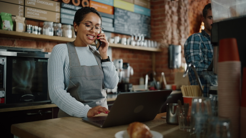 Latin American Coffee Shop Employee Accepts a Pre-Order on a Mobile Phone Call and Writes it Down on Laptop Computer in a Cozy Cafe. Restaurant Manager Browsing Internet and Talking on Smartphone. Royalty-Free Stock Footage #1062437053