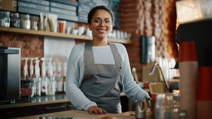 Beautiful Latin American Female Barista with Short Hair and Glasses is Projecting a Happy Smile in Coffee Shop Bar. Portrait of Happy Employee Behind Cozy Loft-Style Cafe Counter in Restaurant. Royalty-Free Stock Footage #1062437077