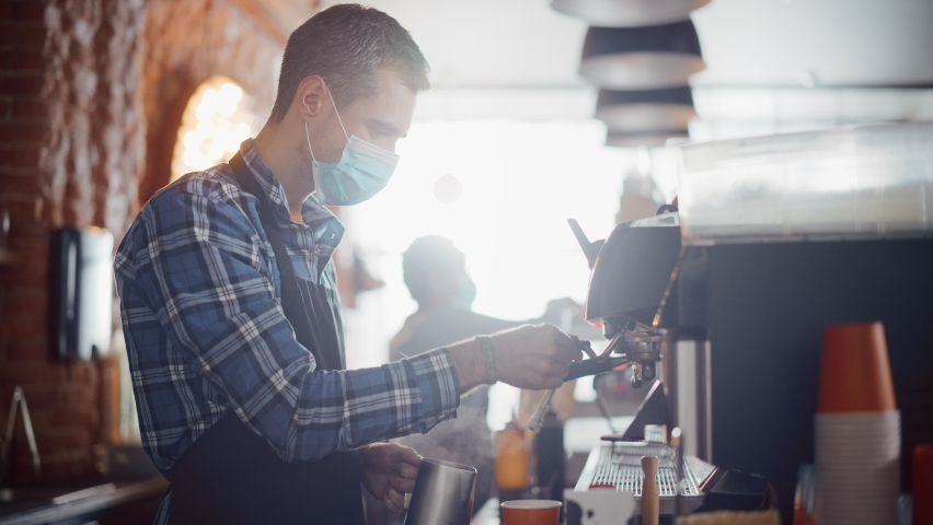 Male Barista in Face Mask is Making a Cappuccino in a Coffee Shop Bar. Lockdown Social Restrictions Concept During Covid-19 Pandemic in Restaurants. Female Cashier Works at a Cafe in the Background. Royalty-Free Stock Footage #1062437209