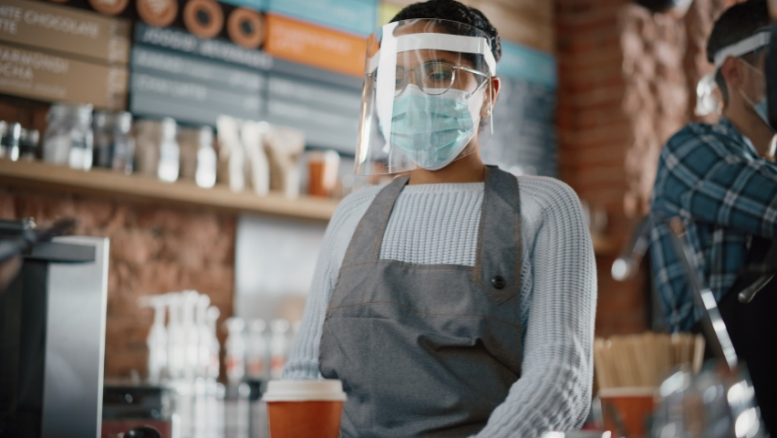 Mandatory Face Masks and Shields in a Coffee Shop During Coronavirus Pandemic. Female Customer Pays for Coffee and Pastry with Contactless NFC Payment Technology on Smartphone to a Barista in Cafe. Royalty-Free Stock Footage #1062437242