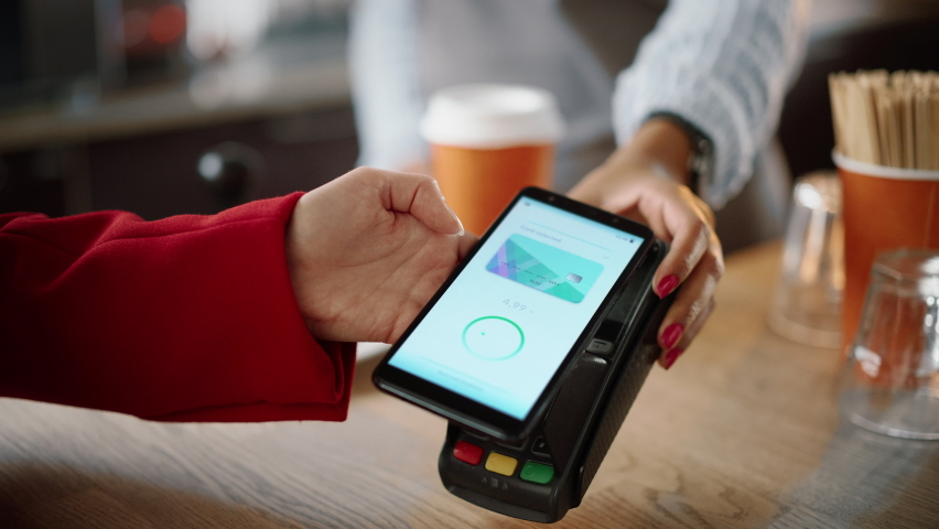 Close Up of a Feminine Hand Holding a Smartphone with an NFC Payment Technology Used for Paying for Take Away Coffee in a Cafe. Customer Uses Mobile to Pay for Latte Through a Credit Card Terminal. Royalty-Free Stock Footage #1062437266