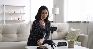 Smiling attractive millennial asian korean mixed female blogger recording make up routine video on smartphone, showing beauty products and tools, recommending cosmetics, modern marketing concept.