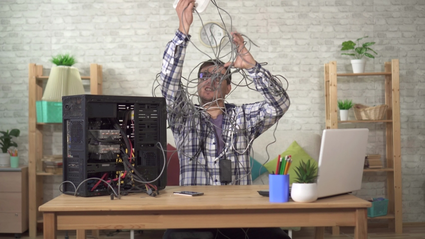 Funny discouraged man in wires with a router in his hands has problems with the Internet