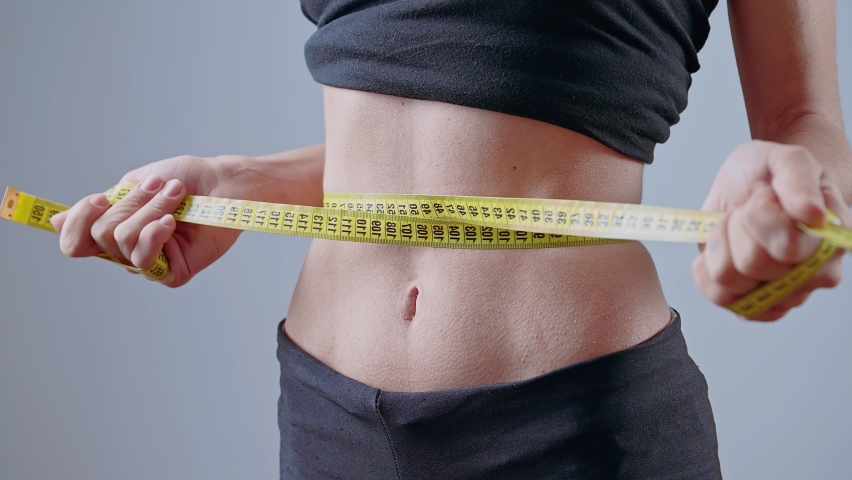 Anorexic young woman tightening measuring tape, torturing herself with diet, bulimia