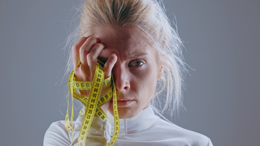 Closeup of girl closing face with measuring tape. Anorexic model holding measuring tape. Dieting eating disorders and weight loss concept