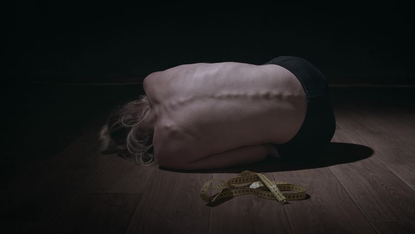 Anorexic young woman lying on the floor. Disorders and weight loss concept. Back view, thin back with spine