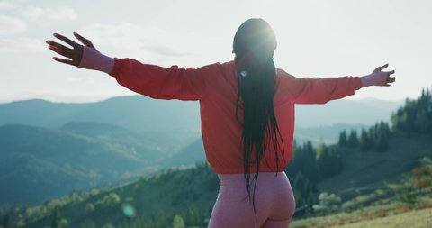 African young sportive woman on top mountain spreading arms enjoying freedom, nature connection and peaceful morning. Sportswoman. Active sports. Beautiful landscape.