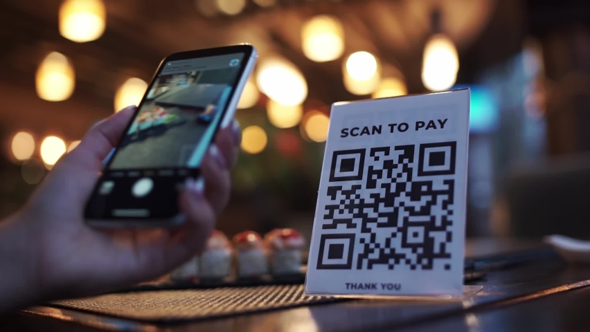 Scanning QR code with smart phone. The woman reads the bar code using the application on the smartphone in cafe Royalty-Free Stock Footage #1062460006