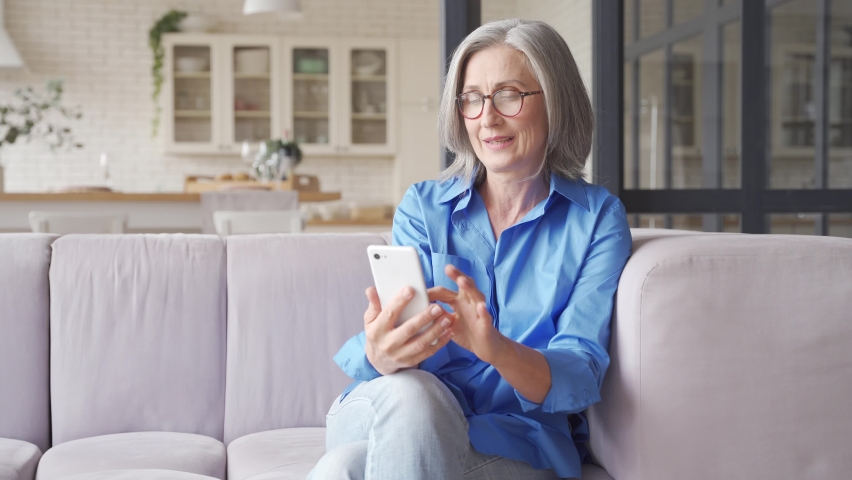 Excited happy mature old 60s woman customer winner holding smartphone using mobile app winning online lottery bid, celebrating success, receiving gift voucher on cell phone sitting on couch at home. Royalty-Free Stock Footage #1062465394