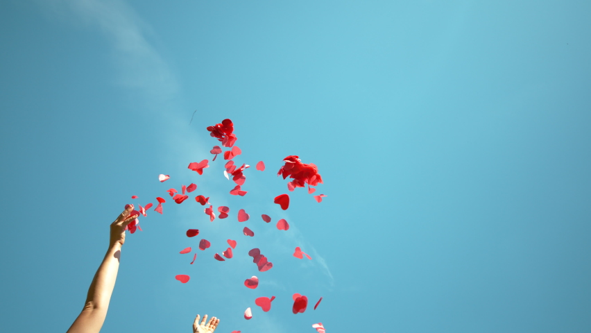 SLOW MOTION, BOTTOM UP: Unrecognizable person throws a handful of red confetti into the sky during a Valentine's day celebration. Woman tosses red heart shaped papers in air during baby gender reveal