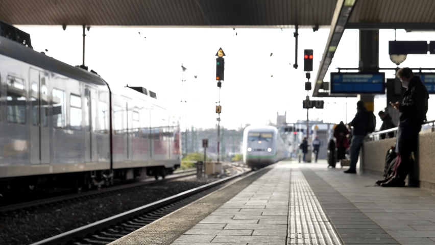 Selective focus at sidewalk of platform in railway station, train arrive and stop, passengers wait for high speed train then get on the train in Düsseldorf, Germany. Royalty-Free Stock Footage #1062468682