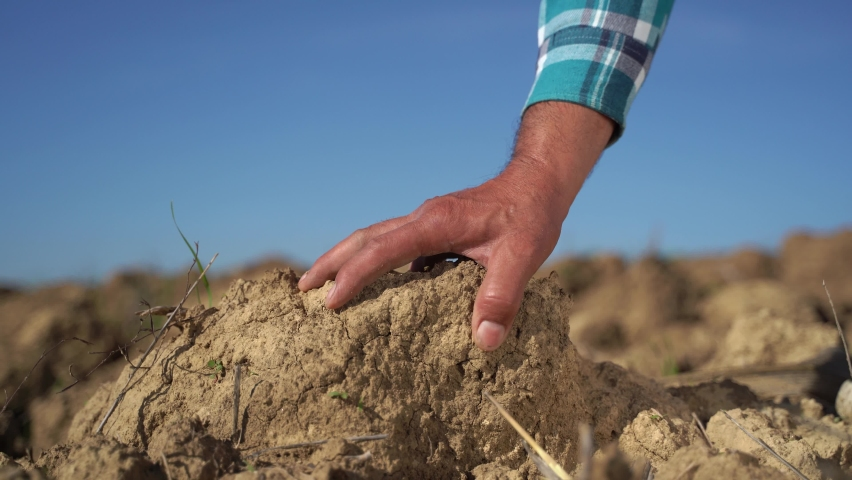 Close up of male hands touching dry ground in an agricultural field, Soil, cultivated dirt, earth, ground, Organic gardening, agriculture. Nature close up. Environmental texture, pattern. Mud on field