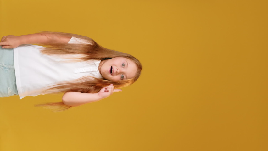 Creative idea. Smart kid. Solution discovery. Aha moment. Vertical portrait of inspired enthusiastic happy girl in white gained insight isolated on orange empty space promotional background.