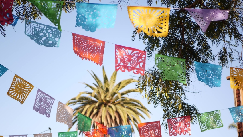 Colorful mexican perforated papel picado banner, festival colourful paper garland. Multi colored hispanic folk carved tissue flags, holiday or carnival. Authentic fiesta decoration in Latin America. Royalty-Free Stock Footage #1062471616