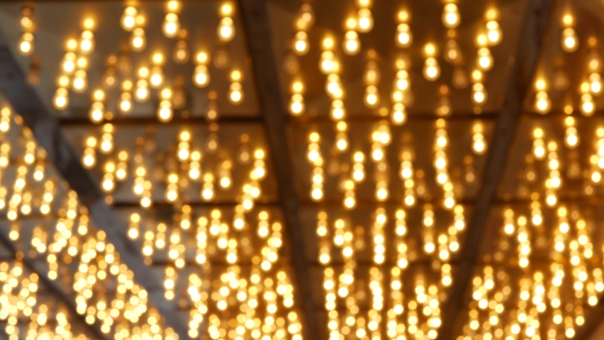 Defocused old fasioned electric lamps glowing at night. Abstract close up of blurred retro casino decoration shimmering, Las Vegas USA. Illuminated vintage style bulbs glittering on Freemont street.   Shutterstock HD Video #1062471682