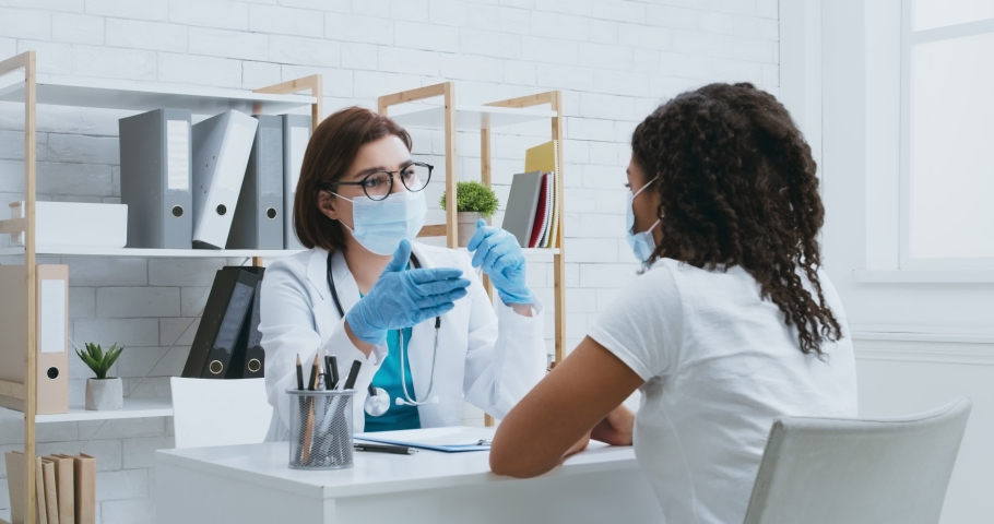 Professional medical consultation. Female doctor in protective mask consulting young african american patient during personal appointment at hospital, slow motion | Shutterstock HD Video #1062471751