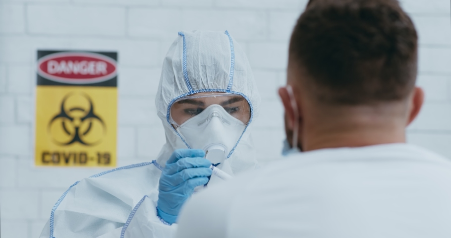 Laboratory worker in hazmat taking PCR throat sample for Covid-19 test from african american patient. Modern medical virology for coronavirus pneumonia or flu cure at science office Royalty-Free Stock Footage #1062471763
