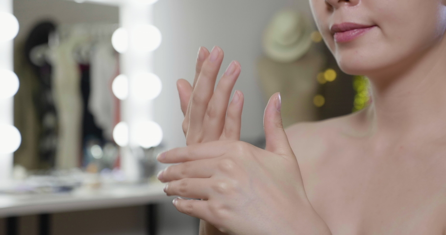 Unrecognized asian beauty woman with hands applying moisturizing cream to skin in backstage dressing room. | Shutterstock HD Video #1062477061
