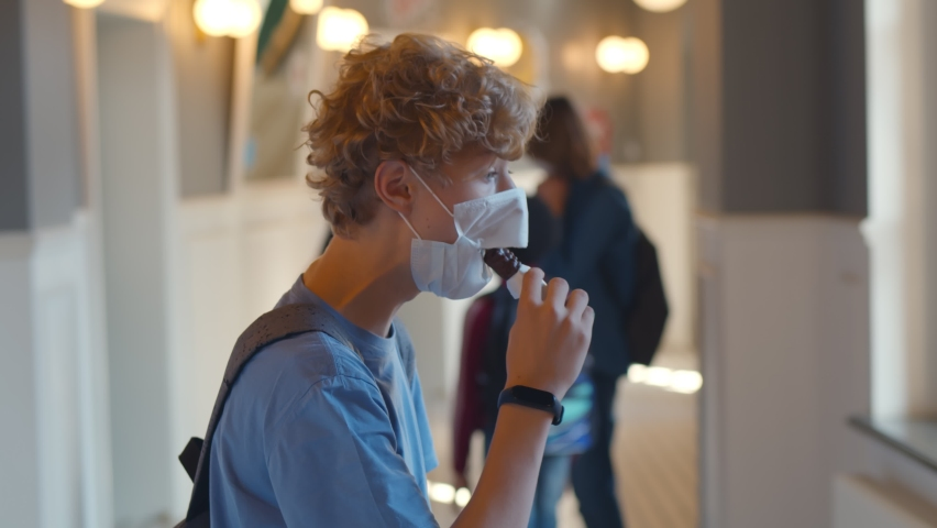 Side view of cute teenage boy with curly hear eating cereal bar wearing safety mask with hole relaxing during break in school hallway. Schoolboy eating lunch in protective face mask