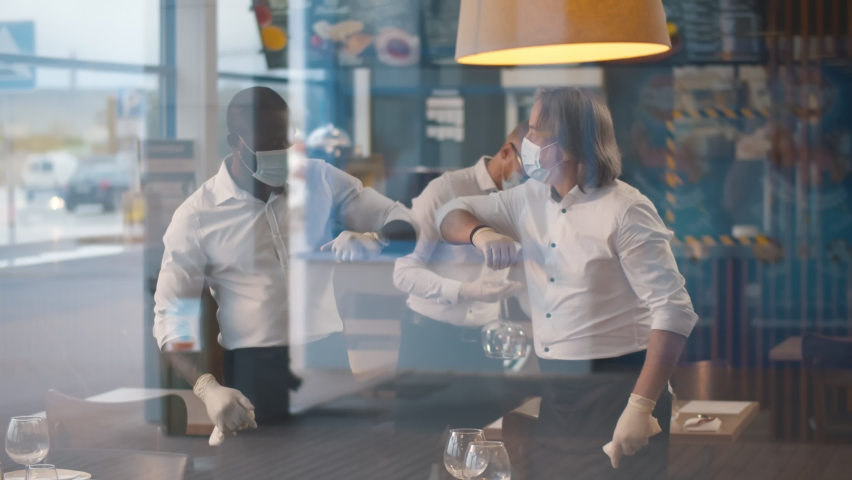 Diverse waiters in medical mask and gloves bumping elbow setting tables in restaurant. View through window of cafeteria staff putting clean dishware on table preparing for reopening after quarantine