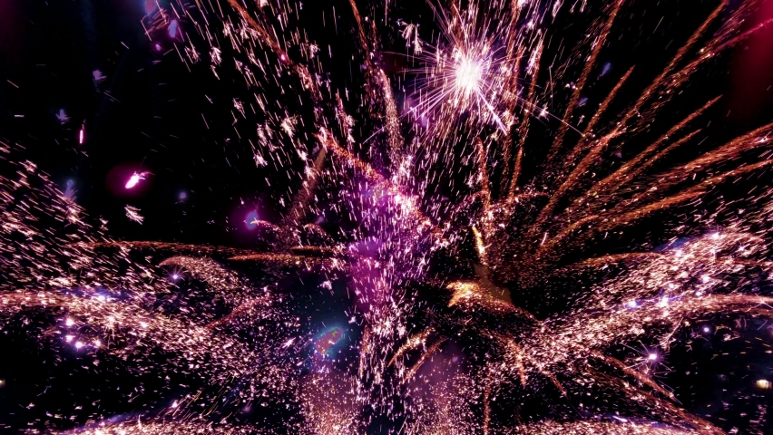 Glowing fireworks show. Fireworks with particles and sparks in the black night sky. Real Shot of fireworks background. Shining fireworks with bokeh. New year's eve firework celebration.  Royalty-Free Stock Footage #1062486307