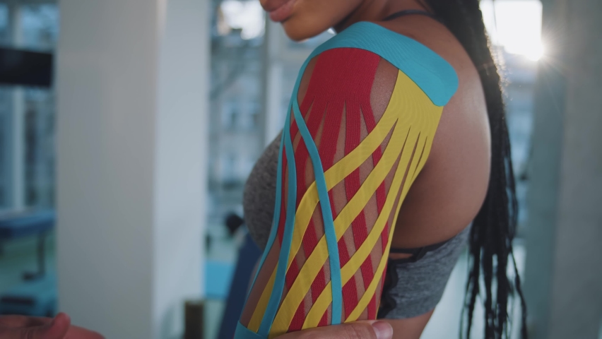 Young black woman athletic with braids stands while her trainer or doctor applies blue, red and yellow kinesio tape on her shoulder after injury. Gym on the background. Sport, health care concept