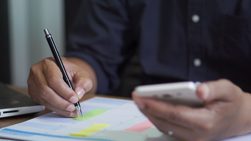 Male hand of planner writing daily appointment On 2021 Calendar book, working space at home. Asian man plan and noted schedule (holiday trip) on the diary at office desk. Calendar for planner concept. Royalty-Free Stock Footage #1062493051