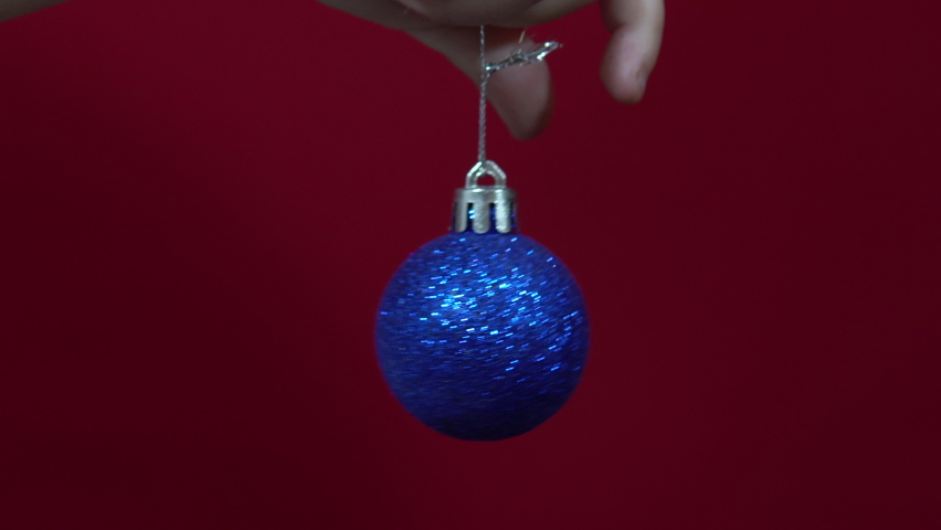 Blue christmas toy in hand on a red background close up Royalty-Free Stock Footage #1062513334