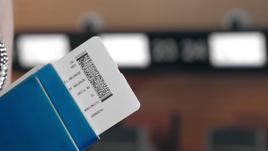 Close-up. woman holds air tickets and passports in her hands against the backdrop of empty check-in counters at the airport. Travelling by airplane.