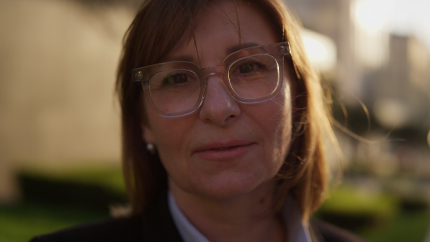 Portrait of an adult female teacher in the courtyard of the university outdoors looking at the camera with glasses. Close-up of a mature female professor on the street at sunset in slow motion near an Royalty-Free Stock Footage #1062519763