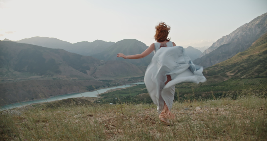Young beautiful girl with red hair wearing white dress running on top of a mountain facing wind blowing her hair and dress and smiling - freedom, adventure, harmony 4k footage Royalty-Free Stock Footage #1062527227