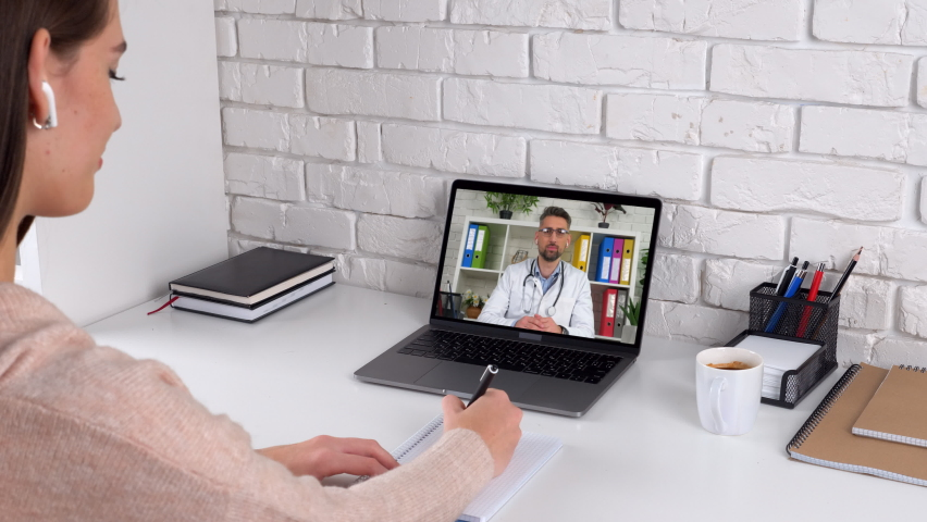 Woman patient client at home writes treatment in notebook listen distance medical worker. Man doctor in laptop screen communicates talk consults remote online conference video call computer webcam | Shutterstock HD Video #1062527335