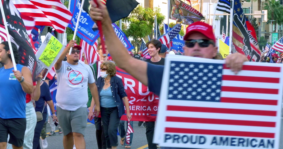 LOS ANGELES, CALIFORNIA, USA - OCTOBER 17, 2020: Crowd of President Donald Trump supporters with flags participates in rally in Beverly Hills, Los Angeles, California, 4K