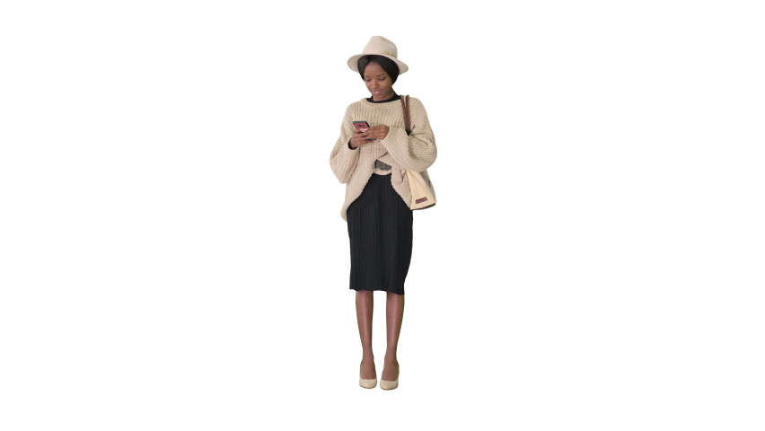 Pretty african american woman in knitted sweater and white hat answering her phone on white background.