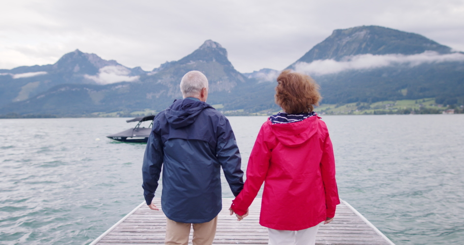 Rear view of senior pensioner couple tourists walking on pier by lake. | Shutterstock HD Video #1062540508